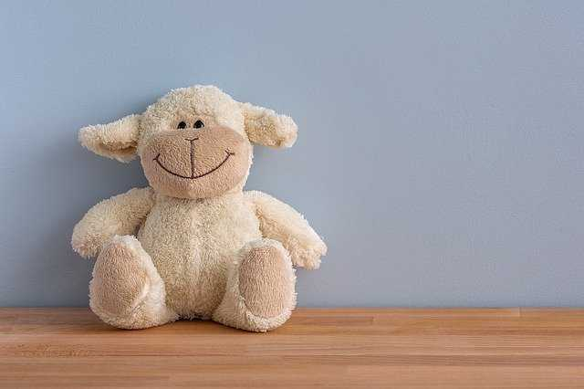 A large brown teddy bear sitting on top of a stuffed animal