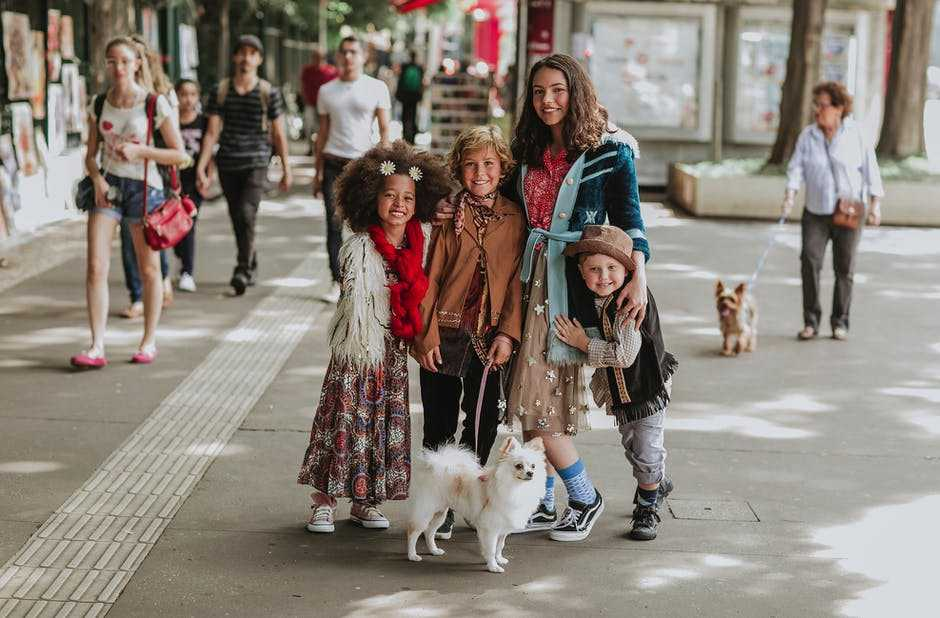 A group of people walking down a street next to a dog